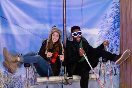 two students pose on a ski lift set for a fun photo