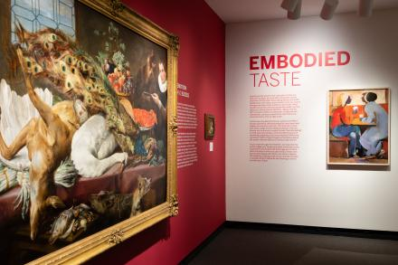 Installation photograph of Embodied Taste. Bright reddish pink font reads
