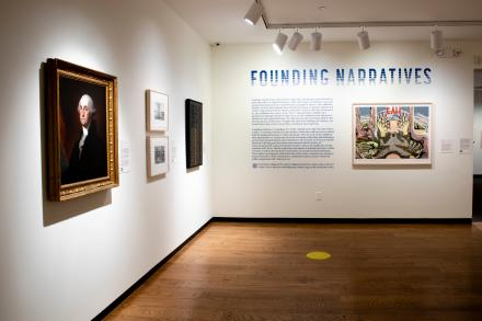Installation photo of Founding narratives exhibition; portrait of George Washington on left; exhibition text in center of image