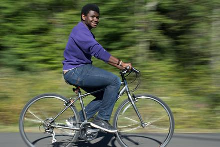 A young man riding on a bicycle