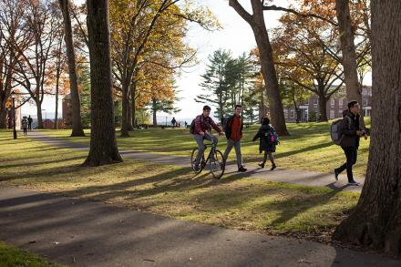 Students walking and riding bikes across the campus quad