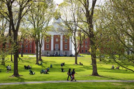 Students sit in groups on the green grass of the quad, among trees, with Johnson Chapel in the background