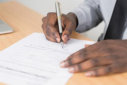 A person's hand filling out a form