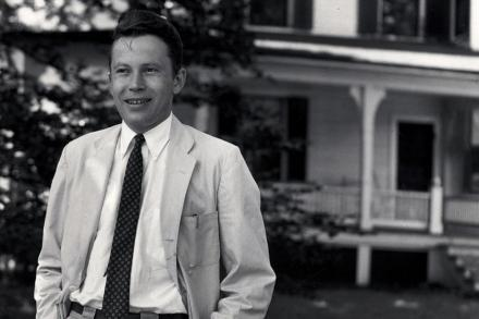 Black and white portrait of young Richard Wilbur wearing a gray suit and black tie