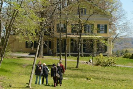 Group of visitors walking towards the yellow brick Dickinson house