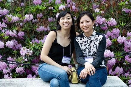 Two alumni sitting a bench side by side with pink flower blossoming behind them
