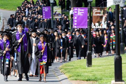Commencement procession led by three students comes up the hill toward the quad