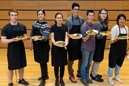 7 people wearing black aprons and holding out plates of food