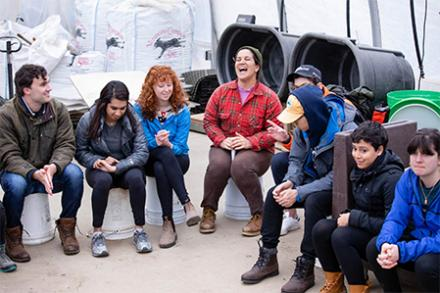 A group of people sitting in a semi-circle talking and laughing