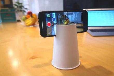 A disposable cup being used as a tripod to hold a cellphone