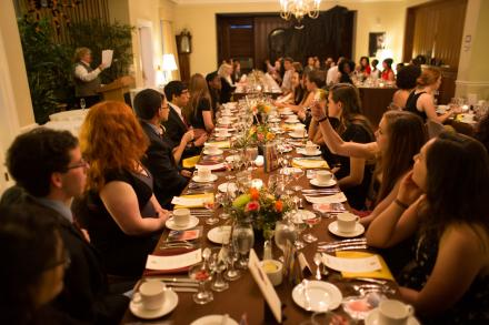 Students seated for dinner at a long, formal table