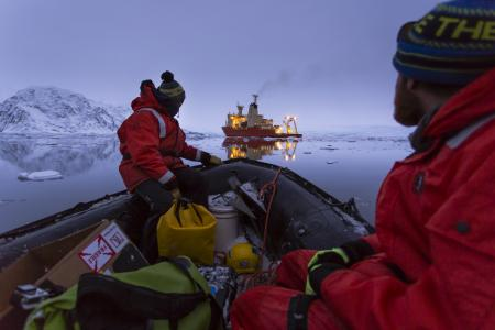 Scientists on a ship sailing down the coast of Antarctica
