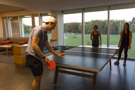 students play ping pong in a recreation room in one of the Greenway Dorms
