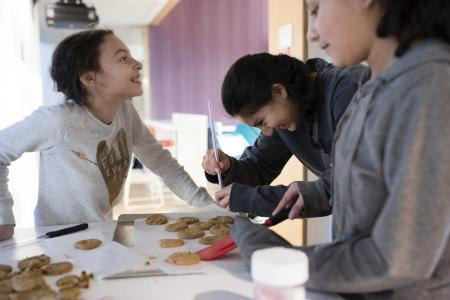 three students making cookies in a kitchen in the Greenway