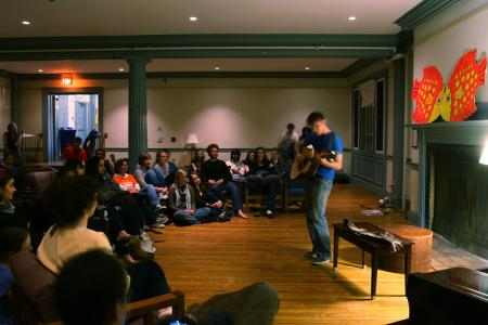 A student plays guitar for an audience in Marsh House cafe