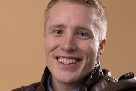 Close up image of Nathan Needham smiling towards the camera.