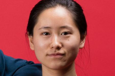 Debbie Wen sits, looking straight into the camera, not smiling.