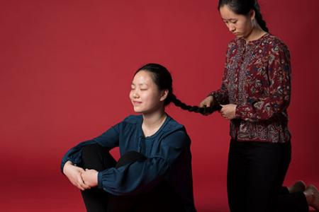 Sisters Faith and Debbie Wen. In this picture Debbie is braiding Faith's hair. She is kneeling behind Faith who is sitting on the ground.