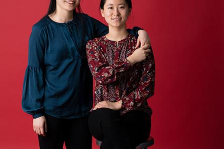 Faith Wen stands beside her seated sister, Debbie Wen. Faith's left arm is draped around Debbie's shoulders, holding hands.