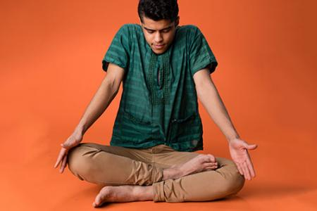 Tomal Hossain sits on the floor, cross-legged, hands extended over his knees, head looking downward.