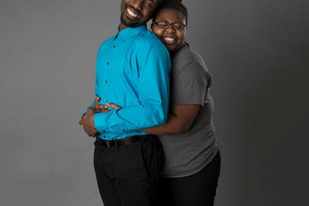 Amir Hall and Nayah Mullings. Nayah is standing behind Amir with her arms around his waist, her head on his shoulder. They are both smiling.
