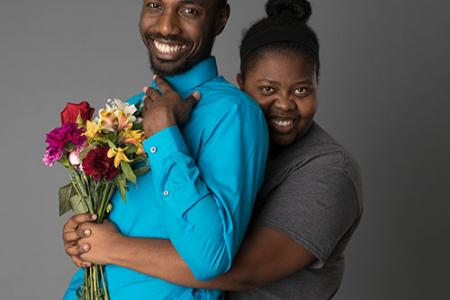 Amir Hall and Nayah Mullings. Nayah embraces Amir from behind, holding a bouquet of flowers in front of his chest.