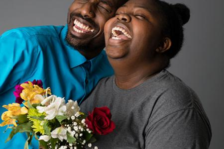 Amir Hall and Nayah Mullings, both smiling, their eyes closed and heads back. Nayah holds a bouquet of flowers.