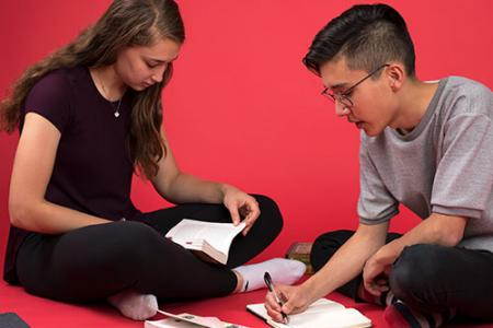 Lauren Tuiskula '17 and Spencer Quong '18 sitting on the floor. Lauren holds a book and Spencer is writing in a journal.