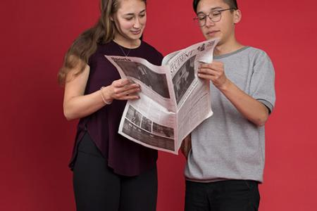 Lauren Tuiskula '17 and Spencer Quong '18 hold a copy of the student newspaper between them, looking at it together.