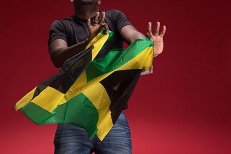 Christopher Lewis posing with the Jamaican flag. He's looking up, both hands in front of him, as if he's dancing.