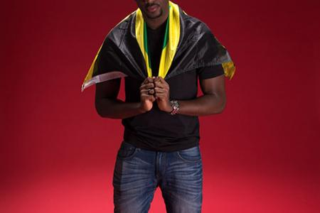 Christopher Lewis posing with the Jamaican flag draped around his neck.