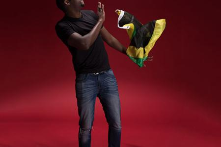 Christopher Lewis posing with the Jamaican flag. He's looking to his left, the flag in his left hand.