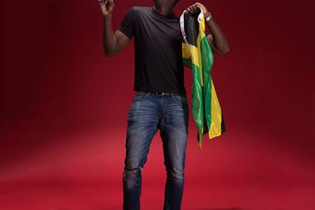 Christopher Lewis posing with the Jamaican flag, looking up and to his right, the flag in his left hand.