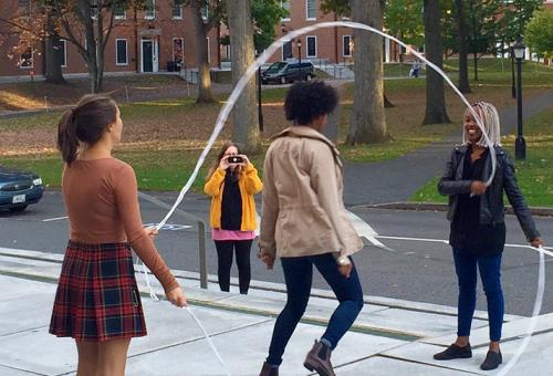 Three student doing Double Dutch in front of Frost Library