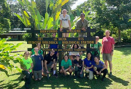 Amherst students posing around a sign at La Selva biological station in Costa Rica