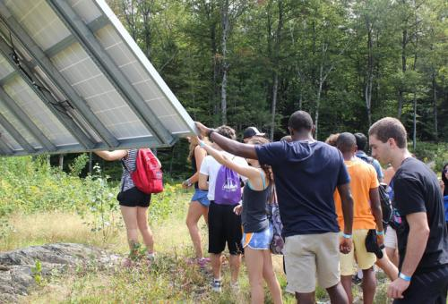 Students touch a solar panel during an orientation program.