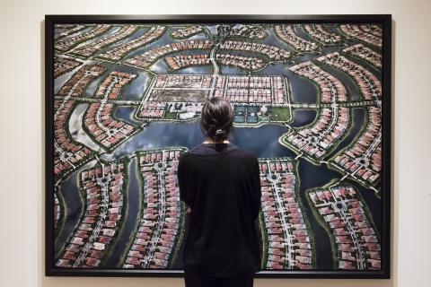 Woman looking at a large photo of a housing development