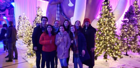8 people standing in front of a purple, big, inflatable mammoth.