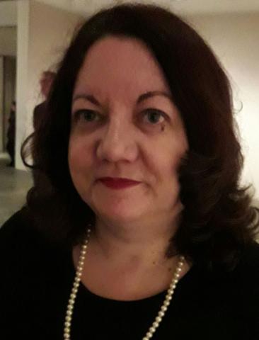 Woman wearing pearls smiling at camera