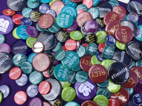 """Multi-colored buttons are displayed in a cluster on top of one another, with phrases like """"Water if Life"""" and """"Times Up"""" on them, indicating favor of various social justice causes"""