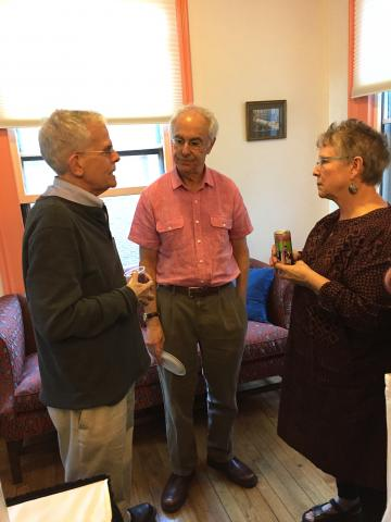 Three faculty members talking at reception