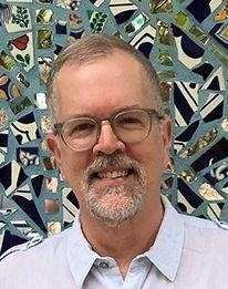 Man wearing glasses with a mosaic wall behind him