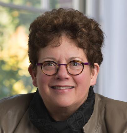 President Biddy Martin, wearing glases, smiles while sitting in front of a window