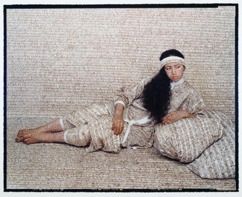A woman with long dark hair leans on the ground.