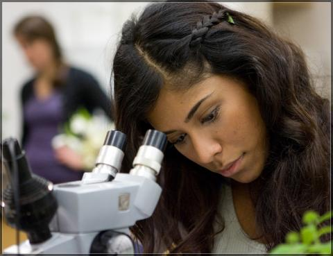 Female student working at microscope.