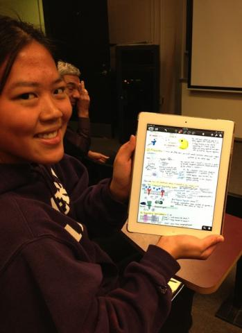 Student showing iPad with notes