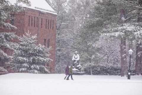 Amherst College campus in a snowstorm. Image of two people walking in front of Charles Pratt Hall and Robert Frost statue