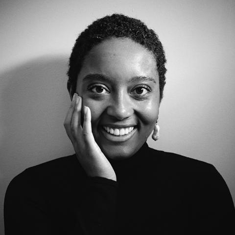 A black and white photo of a smiling Black woman with her hand on her cheek