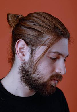 person looking down off picture, beard, long brown hair tied in ponytail wearing a black shirt on burnt red-orange background