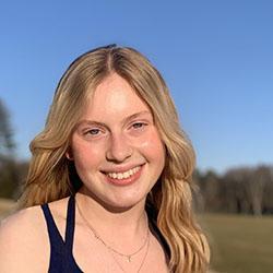 Heloise smiling in a sunlit field